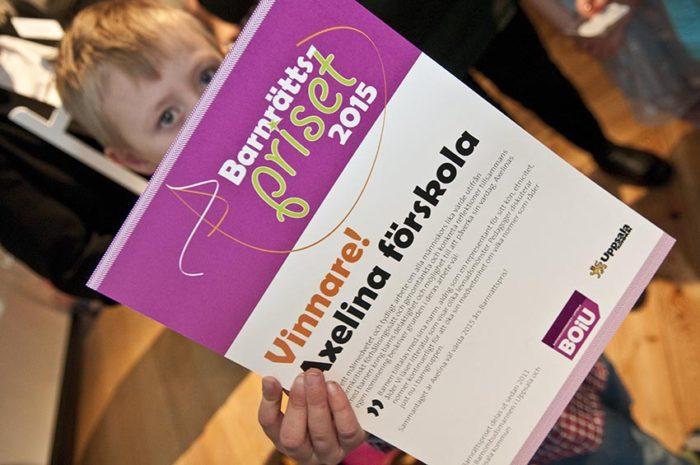 Charlie håller upp diplomet som visar att Axelinas förskola tilldelats 2015 års Barnrättspris av Barnombudsmannen i Uppsala och Uppsala kommun.